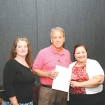 Nora Medina, director of network operations, HUMANA presents a check to Michael Clark, director of business development, Diagnostic Clinic in recognition  of the Clinic's high benchmark standards; Melanie Perkins, credentialing coordinator looks on