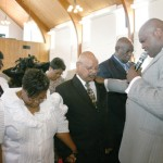 Heads bowed and eyes closed, Reverend L. Dorsett Houston, prays and  ordains Jack Sample, deacon, wife Valencia at his right for support.