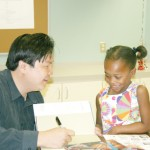 """Woody"" Kuon signs a book for Isabella Olofinlade"